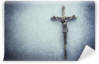 Crucifix of Jesus on the cross with stone background. Symbol of christian religion and belief. Image composed with copy space.