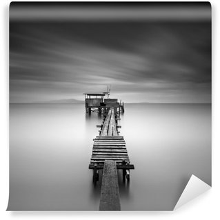 Fine art image of wooden fishing jetty at beach in black and white.Long exposure shot with motion blur. Wall Mural - Vinyl