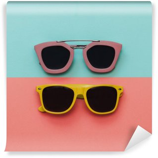 Flat lay fashion set: two sunglasses on pastel backgrounds. Top view. Wall Mural - Vinyl