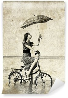 Girl with umbrella on bike. Photo in old image style. Wall Mural - Vinyl