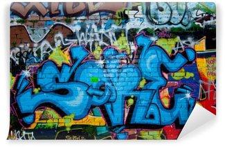 Graffiti detail on the textured brick wall