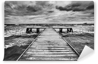 Vinyl Wall Mural Old wooden jetty during storm on the sea. Dramatic sky