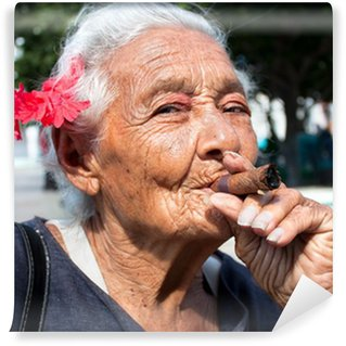 Old wrinkled woman with red flower smoking cigar. Cuba Wall Mural - Vinyl