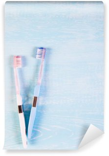 Wall Mural - Vinyl Two toothbrushes and chamomile flowers on a light background. The concept of natural cosmetics for health. You me. View from above