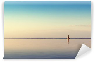 Water landscape with white sailing boat on calm waters in the light of the sunset. Toned and processing photos. Wall Mural - Vinyl