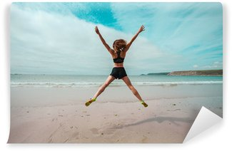 Wall Mural - Vinyl Young woman doing star jumps on the beach