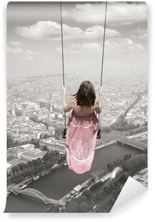 Wall Mural - Vinyl Young woman on a swing on the Paris town backround. Surrealism c