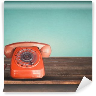 Old retro red telephone on table with vintage green pastel background