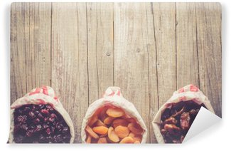 Overhead shot of dried fruits in paper bag on wooden table Washable Wall Mural