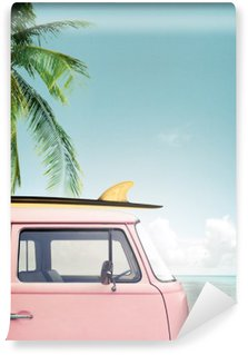 Vintage car parked on the tropical beach (seaside) with a surfboard on the roof Washable Wall Mural