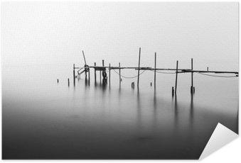 Zelfklevende Poster Een lange blootstelling van een verwoeste pier in het midden van de Sea.Processed in B