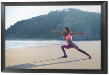Kobieta fitness rozciąganie nóg i praktykujących taniec stwarza na plaży. Czarny lekkoatletka wypracowanie na zewnątrz w stosunku do morza.