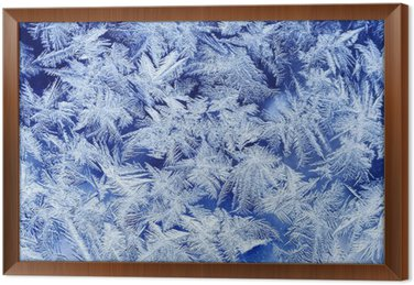 beautiful festive frosty pattern with white snowflakes on a blue background on glass
