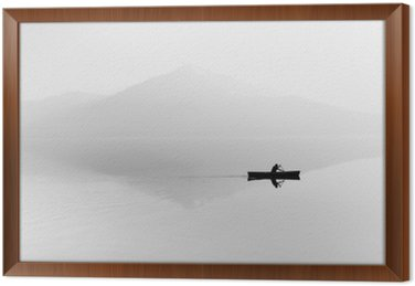 Fog over the lake. Silhouette of mountains in the background. The man floats in a boat with a paddle. Black and white