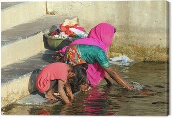 Indian kobieta z córką do prania ubrań w jeziorze