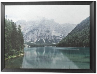 Braies lake with green water and mountains with trees