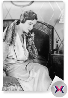 Młoda kobieta siedzi na łóżku w sypialni, mówiąc na telefon