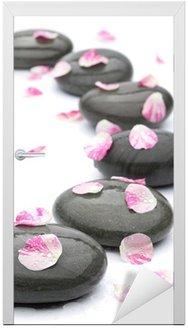 Kamienie Spa z płatków róży na białym tle.