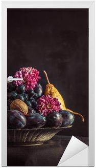 Miska owoców z winogron i śliwek na ciemnym murze