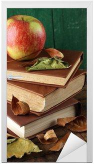 Jabłko z książek i suchych liści na tle drewniane