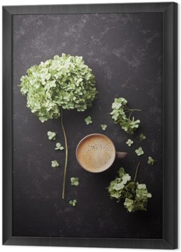 Composition with cup of coffee and dried flowers hydrangea on black vintage table from above, flat lay