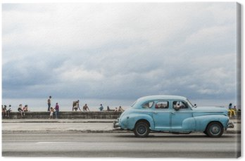 HAVANA, CUBA - MAY 18, 2011: Classic vintage American car serving as taxi drives along the seafront Malecon, a popular place for socializing in Central Havana.