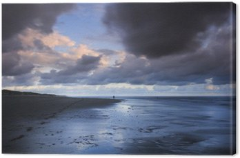 Długi ekspozycji zdjęcia profesjonalny fotograf w akcji na pięknej plaży w samym środku burzy podczas zachodu słońca.