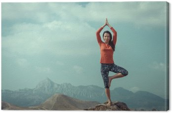 The girl is engaged in yoga on a background of ocean, tree pose