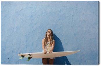 Szczęśliwa dziewczyna z surfer deska surfingowa przed niebieską ścianą