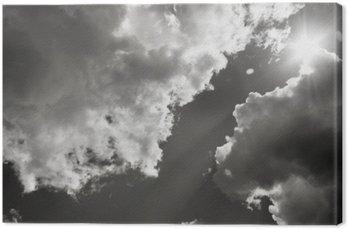 Słońce przebija się przez chmury. Czarno-białe zdjęcie