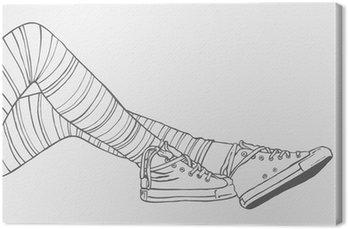Nogi kobiet w pasiastych pończochach i trampki