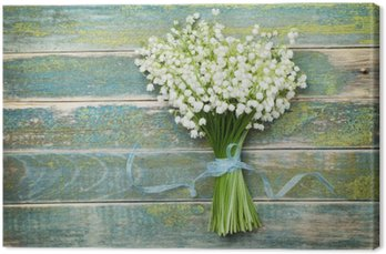 Beautiful bouquet of flowers lily of the valley on vintage wooden table from above, rustic background