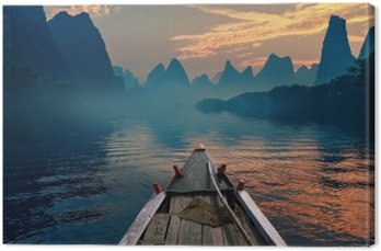 A boat riding in a river during sunset next to a beautiful mount