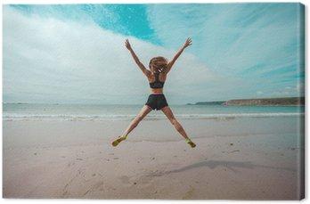 Młoda kobieta robi gwiazda skoków na plaży