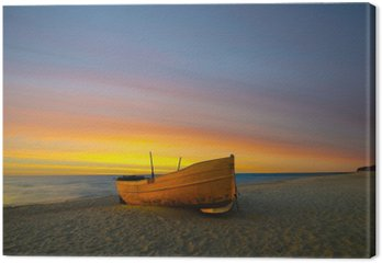 Pomarańczowa łódź rybacka na plaży o zachodzie słońca