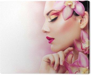 Piękna dziewczyna z kwiatów orchidei. idealny makijaż
