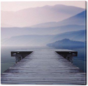 Drewniane molo nad jeziorem, na miejscu w obliczu piękna góra na mglisty zimowy poranek